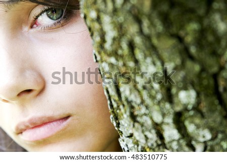 An enigmatic girl with green eyes looking sideways to the camera, her face partly obscured by a green tree bark that matches her eye.