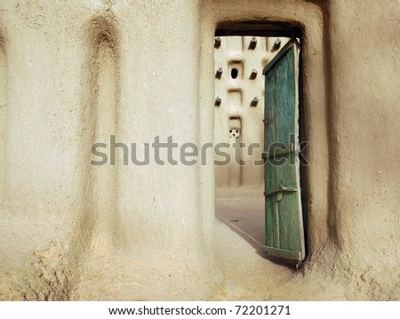 An entrance door into a mud mosque in a Dogon village in Mali - stock photo