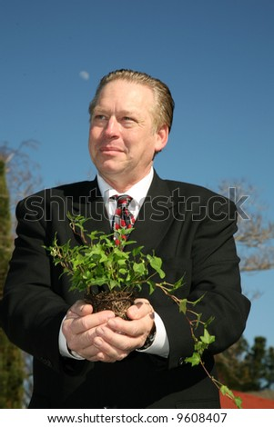 an enviromently friendly business man in a nice suit holds a green plant to save the earth from Global Warming - stock photo