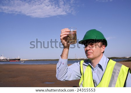 An environmental engineer on the mudflats examining an unusual  plant specimen found on the mudflats in the background is a tanker moored, wearing a yellow reflective vest and green safety helmet. - stock photo