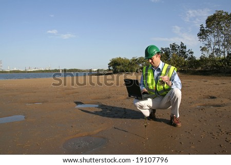 An environmental engineer, wearing protective clothing on his laptop computer analyzing data from the  mudflats in the estuary. - stock photo