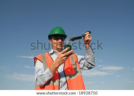 An environmental engineer, wearing protective clothing, placing a soil sample into a specimen jar, containing a green fluid with a beautiful blue sky behind him. - stock photo
