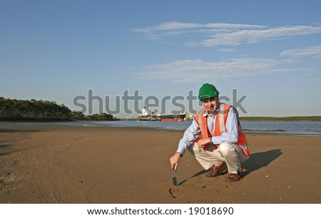 An environmental engineer, wearing protective clothing, taking a soil sample, with a beautiful blue sky behind him and a large ship moored behind him. - stock photo