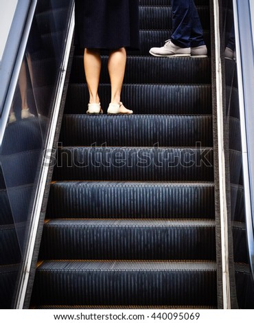 An escalator with office workers (moving up) symbolizing the concept of the career ladder or career path.  - stock photo