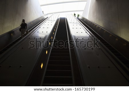 An escalator with passengers moves through oval tube of light to the Washington D.C. Metrorail commuter trains  - stock photo