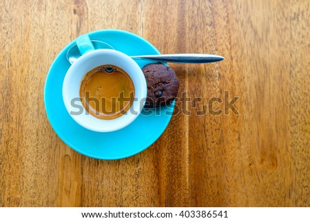 An espresso in a turquoise cup on a wood table
