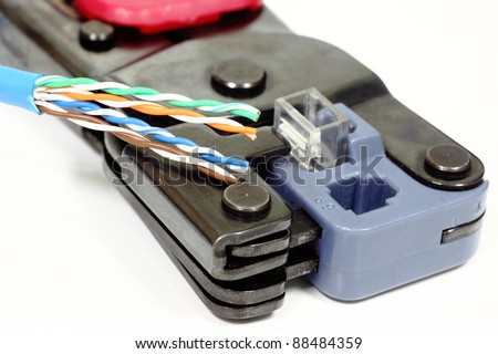 An ethernet cable wire ready to be assembled to a loose RJ45 head inside the network crimper device on white - stock photo