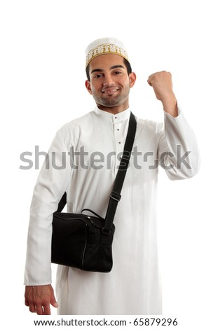 An ethnic arab or south asian man dressed in traditional cultural clothing.  He is smiling and one arm clenched in a victory fist of success - stock photo