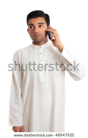 An ethnic businessman in a kurta, dishdasha, thobe, robe, traditional attire, is making a phone call using a mobile phone.  He is glancing sideways. - stock photo