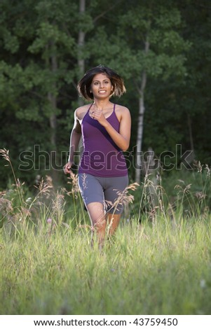 An ethnic looking woman in her 20's running - stock photo