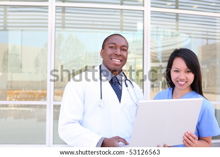 An ethnic medical man and woman team outside hospital on laptop computer
