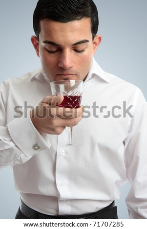 An ethnic mixed race professional man smelling the bouquet of wine in a glass - stock photo
