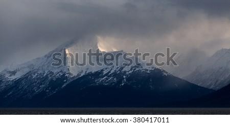 An evening snow storm dusts the mountains along Turnagain Arm near Anchorage, Alaska. - stock photo