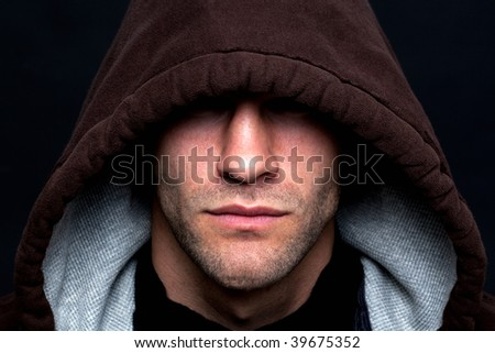 An evil looking man wearing a hooded top with his eyes hidden against a black background. - stock photo