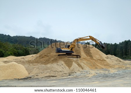 an excavator atop a sand hill in an open sand-mine in a jungle clearing - stock photo