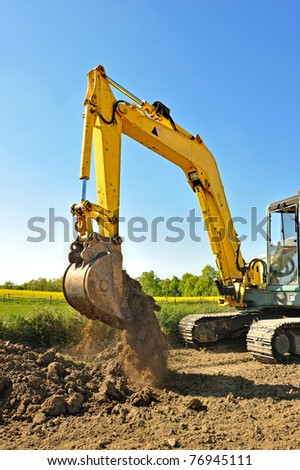 an excavator doing work in the countryside - stock photo