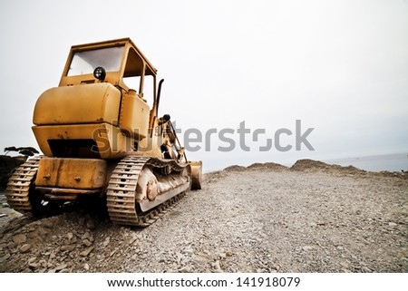 an excavator on the beach - stock photo