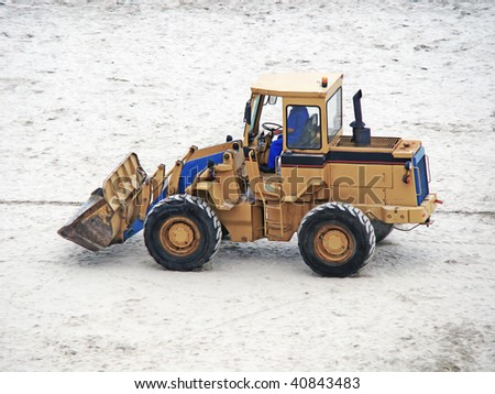an excavator parked on the sand - stock photo