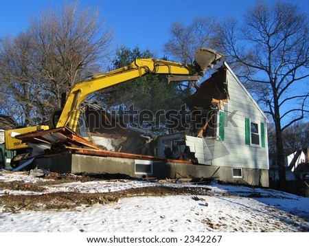 an excavator rips a house apart