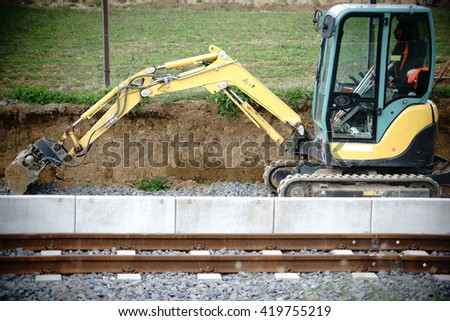An excavator stands at a construction site of a railway line / Excavators at the railway works              - stock photo