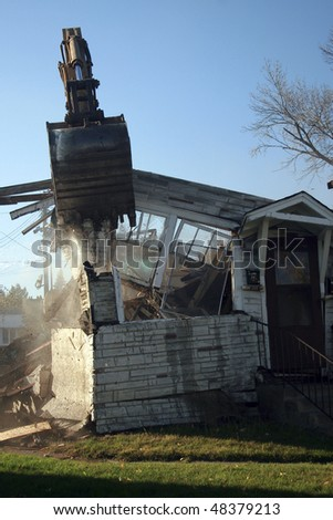 an excavator tearing down a house