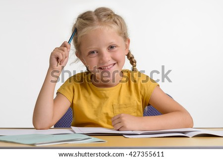 An exceptional child during her studying process which gives her a lot of pleasure. The love for education. Little caucasian girl with fantastic smile looks in the camera.  - stock photo