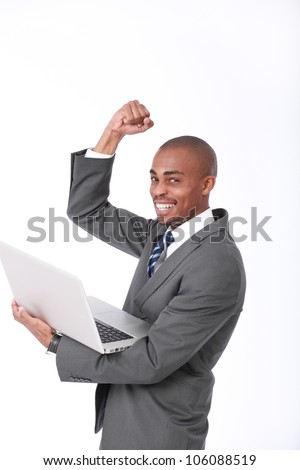 An excited african businessmen holding a laptop while holding his hand up in the air in a triumphant pose - stock photo