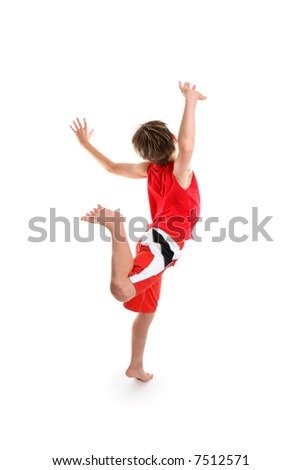 An excited  boy feeling good is  leaping for joy hands raised in the air.
