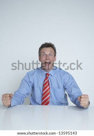 An excited businessman at his desk - stock photo