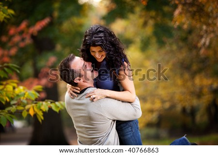 An excited couple giving each other a big hug in a park