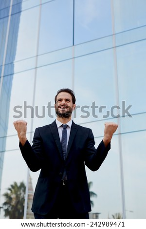 An excited man with winner spirit celebrating success, happy businessman with his arms raised standing near office building, overjoyed businessman raising his arms in victory outside a office building - stock photo