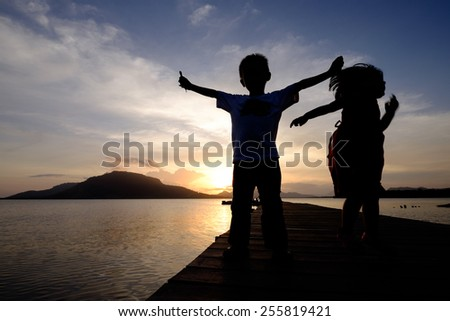 an excited siblings (boy spreads his arms with toys in both hand and his jumping younger sister) during sunrise   - stock photo