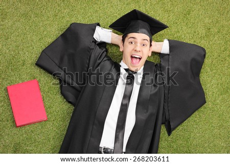 An excited student in graduation gown, lying on green grass with a book next to him and looking at the camera  - stock photo