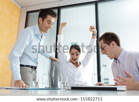 An excited young business team celebrating their success - stock photo