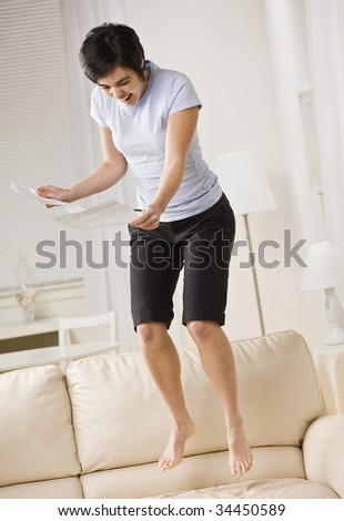 An excited young woman is reading a piece of paper and jumping up and down on the couch.  She is looking away from the camera.  Vertically framed shot. - stock photo