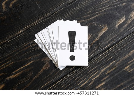 An exclamation mark on the paper and a few pieces of paper on a wooden table in the middle - stock photo
