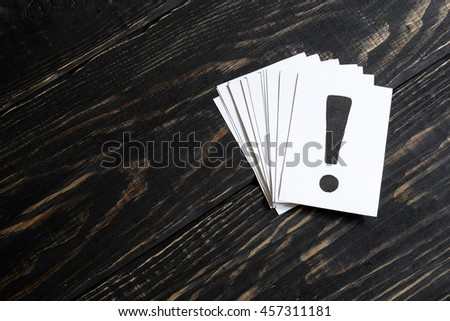 An exclamation mark on the paper and a few pieces of paper on a wooden table on the right - stock photo