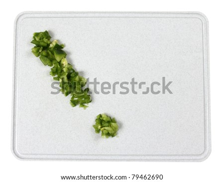 An exclamation mark with green peppers on a cutting board - stock photo