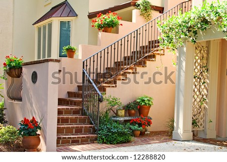 An exclusive neighborhood in Harbour Town, Hilton Head, SC.  Condominium entrance stairway decorated with flowers. - stock photo