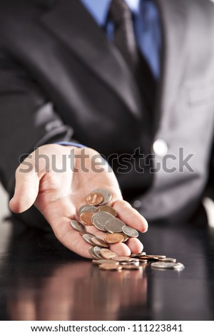 An executive holds an overflowing amount of change in his outstretched hand. - stock photo