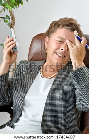 An executive type businesswoman on the phone with a splitting headache. - stock photo