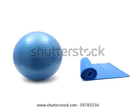 An exercise mat and a fitball isolated against a white background - stock photo