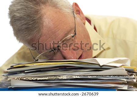 An exhausted senior businessman has fallen asleep on his work. - stock photo