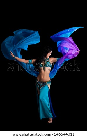 An exotic belly dancer wearing a teal and royal blue costume. She is dancing with a flowing blue and purple silk veil. Shot in the studio on a black background. - stock photo