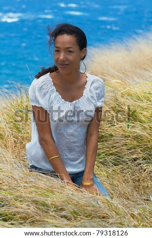 An exotic Hawaiian woman sits in the tall grass on a cliffside overlooking the ocean in Maui, Hawaii. Vertical image orientation. - stock photo