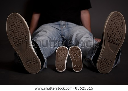 An expecting dad showing off the same shoes he got for his son to be that match his. - stock photo
