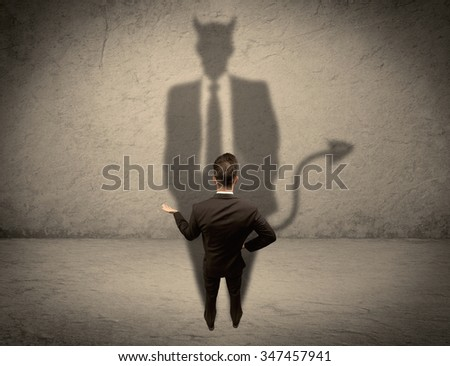 An experienced tricky businessman in suit looking at his devil desguise shadow reflected on the wall concept - stock photo