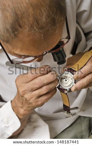 An experienced watch repair man  Watch repair done with great care - stock photo