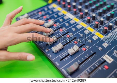 An expert adjusting audio mixing console - stock photo