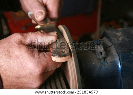 an Expert Custom Knife Maker shapes and sands the handle on a knife he is making for an exclusive client.  - stock photo